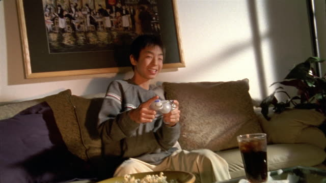 Medium shot teenage boy on couch playing video game / Honolulu, Hawaii