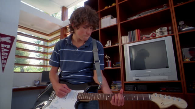 Medium shot teenage boy playing electric guitar in bedroom and making faces