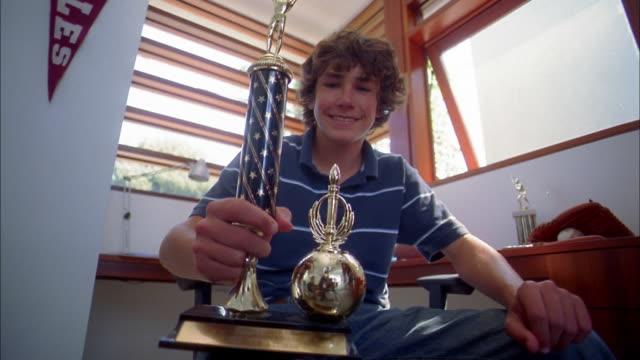 Medium shot teenage boy smiling and holding trophy toward CAM