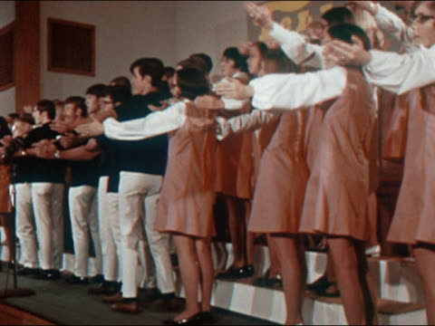 1970 medium shot teenage boys and girls chorus standing on risers / performing choreographed routine on stage - chorsänger stock-videos und b-roll-filmmaterial