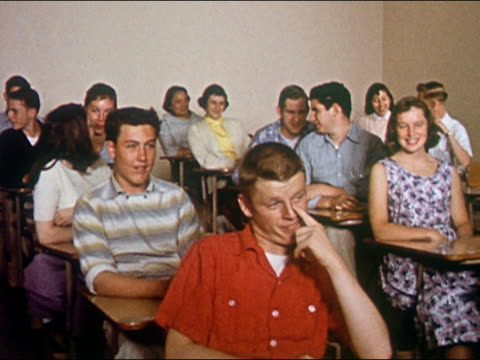 1956 medium shot teenage boys and girls sitting at desks in classroom / giggling amongst each other - studente di scuola secondaria allievo video stock e b–roll