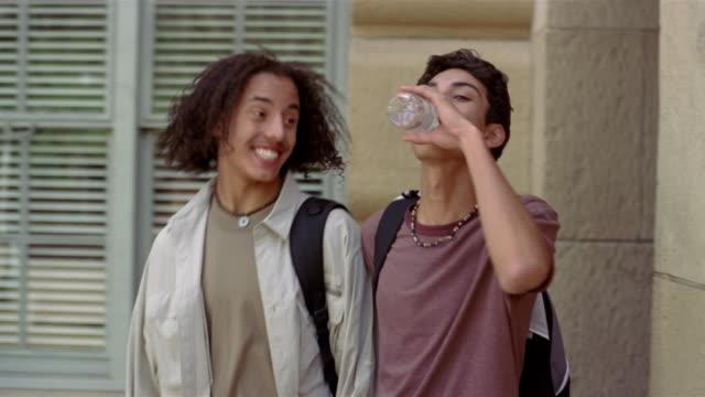 Medium shot teenage boys walking around corner and talking / one boy drinking bottled water