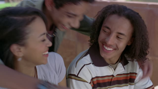 Medium shot teenage couple smiling at each other / boy coming up from behind and hugging them