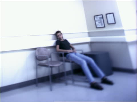 vidéos et rushes de medium shot teenage girl seated in chair in hospital waiting area stretched out, checks watch - salle d'attente