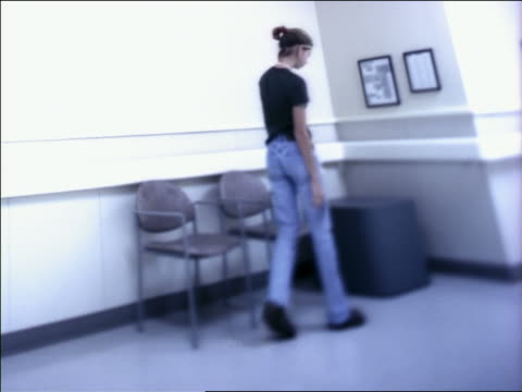medium shot teenage girl sitting on chair in hospital waiting are and sipping on straw in cup - solo adolescenti femmine video stock e b–roll