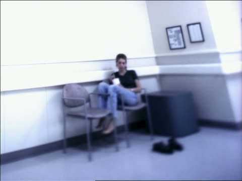 medium shot teenage girl sitting with legs over arm of chair in hospital waiting area and sipping on straw in cup - solo adolescenti femmine video stock e b–roll