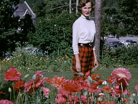 1951 medium shot teenage girl standing among poppies in flower garden in waterton lakes national park / alberta, canada  - 1951 stock videos & royalty-free footage