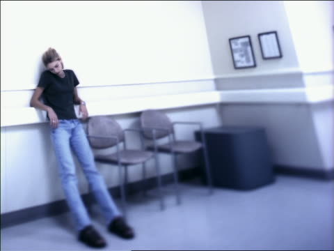 medium shot teenage girl standing in hospital waiting area next to chairs with elbows on ledge - weiblicher teenager allein stock-videos und b-roll-filmmaterial