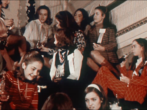 1970 medium shot teenage girls sitting on staircase chatting and drinking bottles of Coca-Cola
