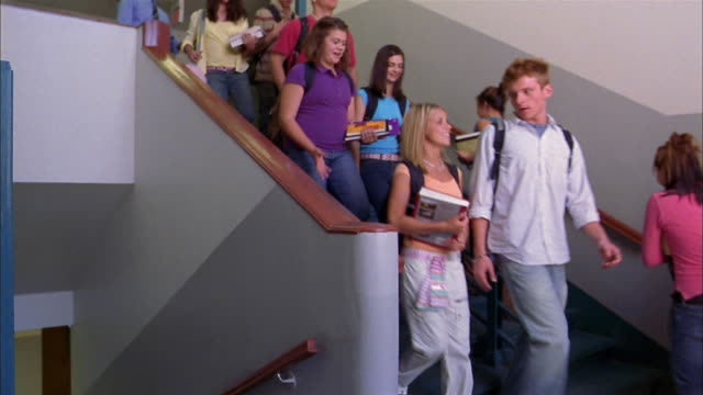 Medium shot teenage students and teachers walking up + down staircase