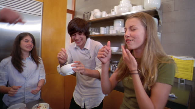 medium shot teenagers eating ice cream sundaes in kitchen - 16 17 jahre stock-videos und b-roll-filmmaterial