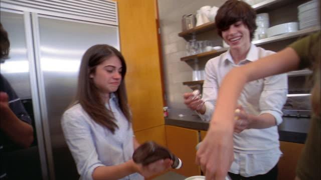 medium shot teenagers making ice cream sundaes and eating whipped cream from bottle - サンデー点の映像素材/bロール