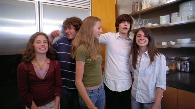 medium shot teenagers posing in kitchen and smiling at cam - organised group photo stock videos & royalty-free footage