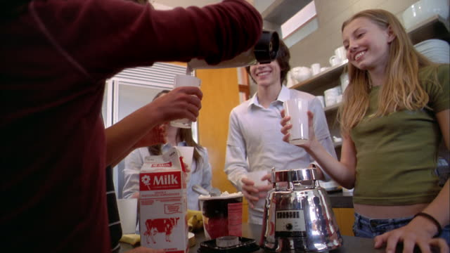 medium shot teenagers pouring chocolate milk shakes from blender and drinking toast - pouring milk stock videos & royalty-free footage