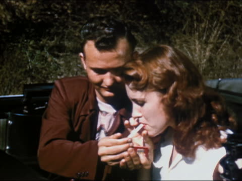 1951 medium shot teenagers smoking joint in convertible car