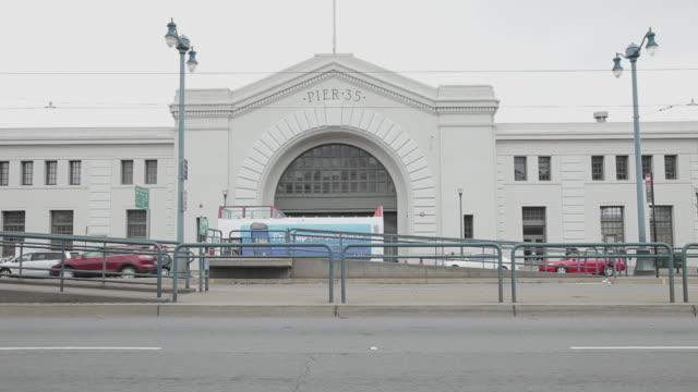 medium shot the entrance to pier 35 in san francisco - trolleybus stock-videos und b-roll-filmmaterial
