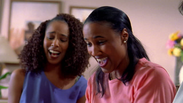 medium shot three black women sitting with one opening presents - birthday gift stock videos & royalty-free footage