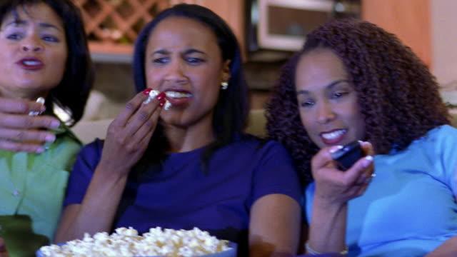 medium shot three black women watching television and eating popcorn - おやつ点の映像素材/bロール