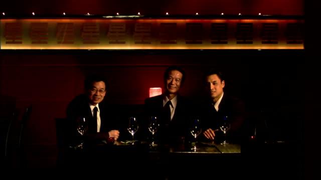 vídeos de stock e filmes b-roll de medium shot three businessmen at restaurant table - sentar se