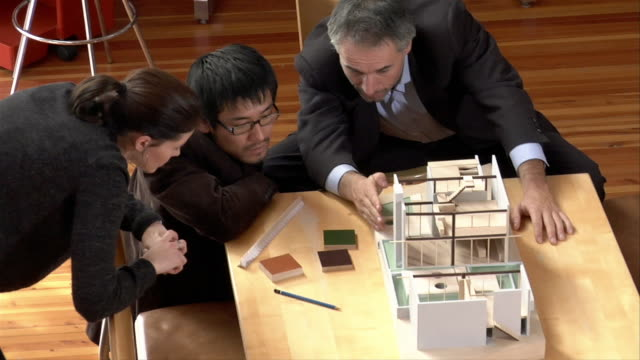 medium shot three businesspeople talking and looking at architectural model - female with group of males stock videos & royalty-free footage