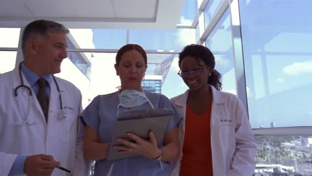 medium shot three doctors talking and walking down hospital hallway/ panama city, panama  - doctor multitasking stock videos & royalty-free footage