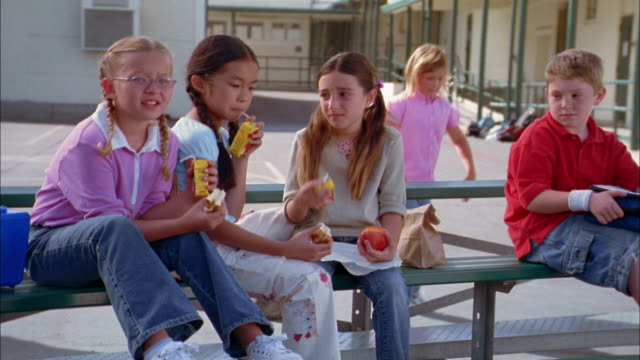 Medium shot three girls eating lunch and glaring at boy on bench at playground