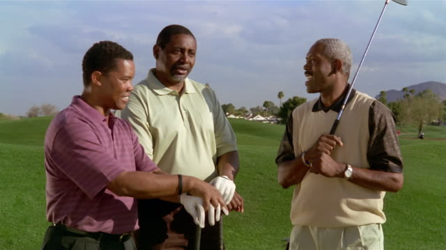 medium shot three mature men talking on golf course - golf glove stock videos and b-roll footage