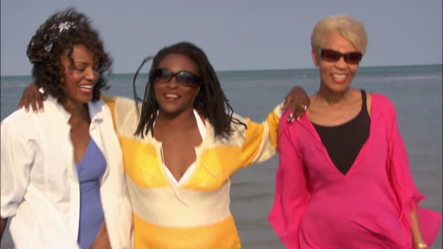 Medium shot Three mature women hugging and talking on beach / Miami, Florida, USA