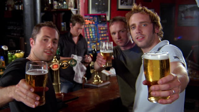 vidéos et rushes de medium shot three men looking at cam, holding beer glasses up, toasting and drinking w/bartender in background - angleterre