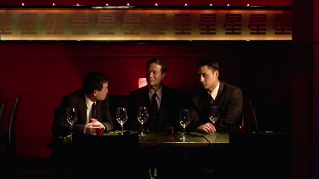 medium shot three men sitting having business meeting in restaurant - business lunch stock videos & royalty-free footage