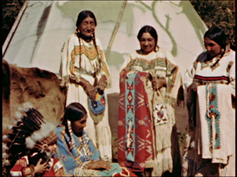 Medium shot three Native American women stand near tent and watch seated woman sew / AUDIO