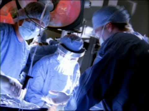 medium shot three surgeons operating in operating room with associate hanging up equipment in background - 手術服点の映像素材/bロール