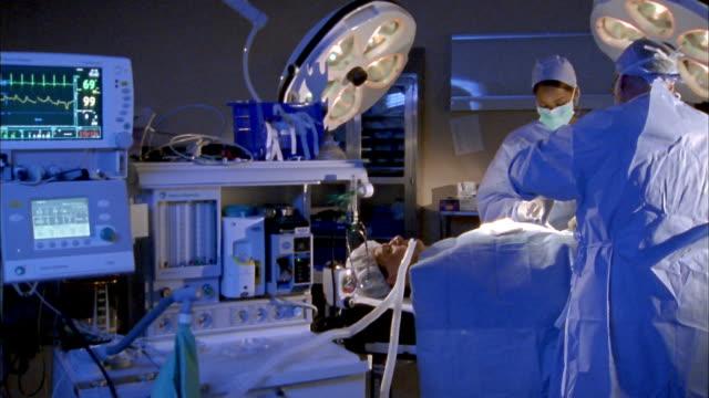 vídeos de stock e filmes b-roll de medium shot three surgeons performing abdominal surgery operation on patient w/medical device in foreground - bata cirúrgica