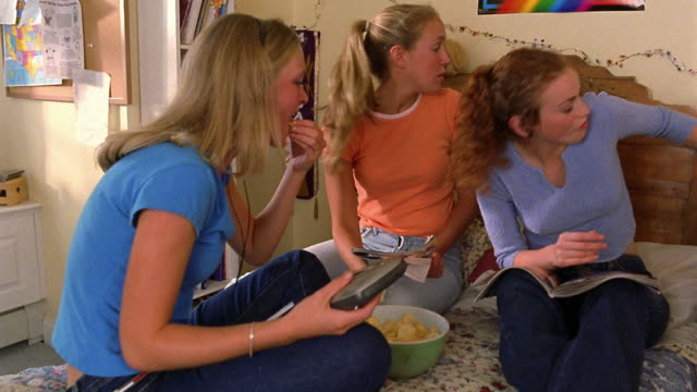 Medium shot three teen girls sitting on bed, eating, reading, listening to music / one girl answering phone