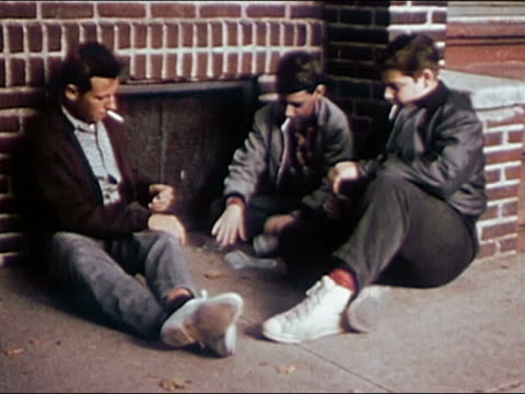 1955 medium shot three teenage boys sitting on sidewalk smoking cigarettes and playing cards