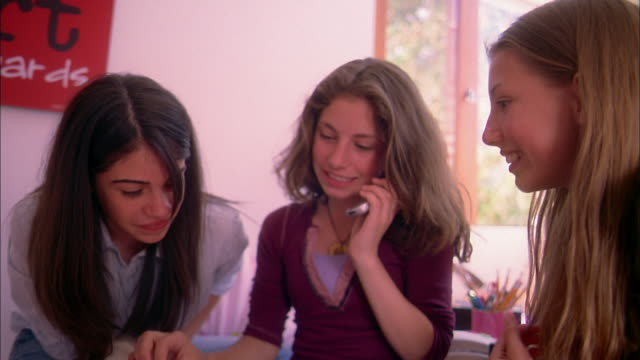 medium shot three teenage girls passing mobile phone and talking in bedroom - 2004 stock-videos und b-roll-filmmaterial
