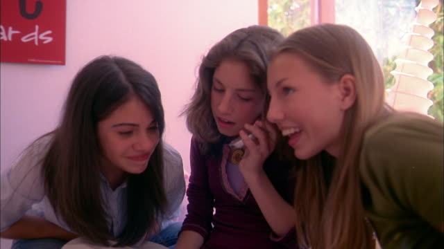stockvideo's en b-roll-footage met medium shot three teenage girls sitting in bedroom and listening to one girl talking on mobile phone - 2004
