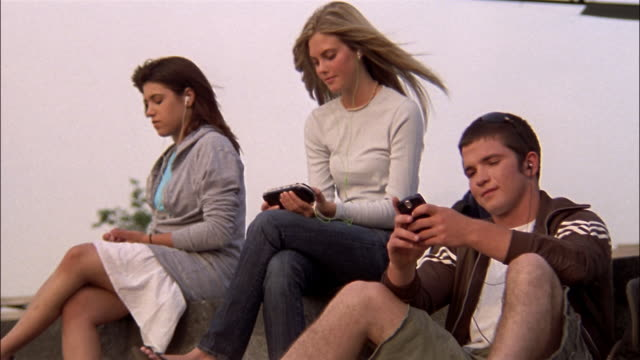 Medium shot three teens sitting using electronic devices