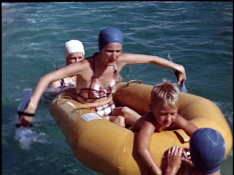 1954 medium shot three women and young boy floating on inflatable raft in swimming pool / california, usa  - swimming cap stock videos and b-roll footage