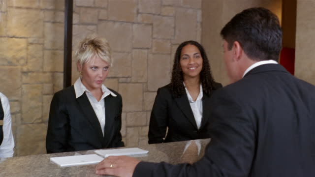 medium shot three women at hotel reception desk / woman helping businessman check in - ホテル点の映像素材/bロール