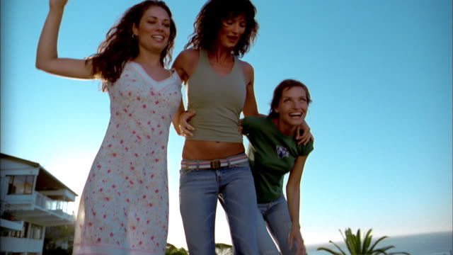 Medium shot three women jumping arm-in-arm outdoors