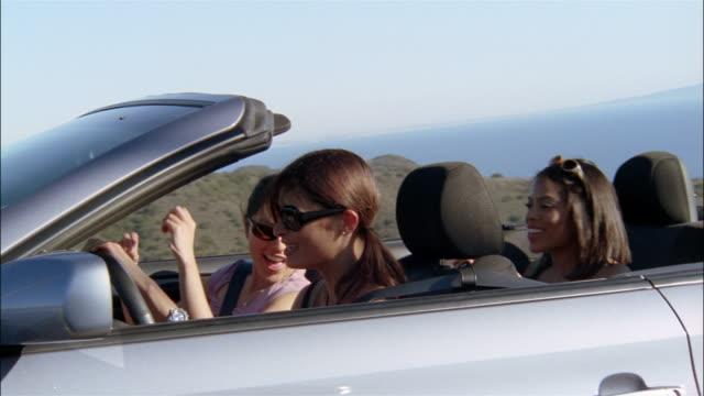 stockvideo's en b-roll-footage met medium shot three women riding in convertible / dancing to music - rondrijden