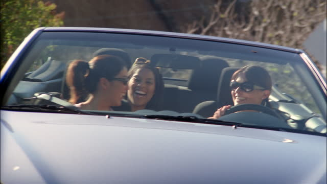 Medium shot three women riding in convertible / laughing and clapping to music