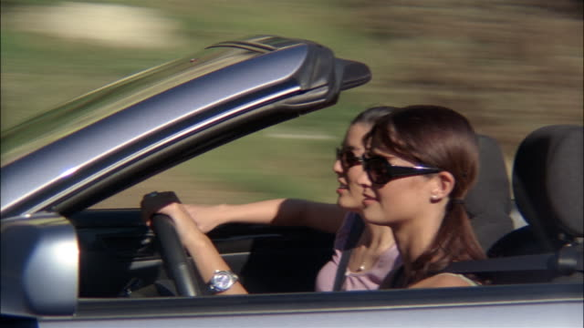 vidéos et rushes de medium shot three women riding in convertible - aller tranquillement