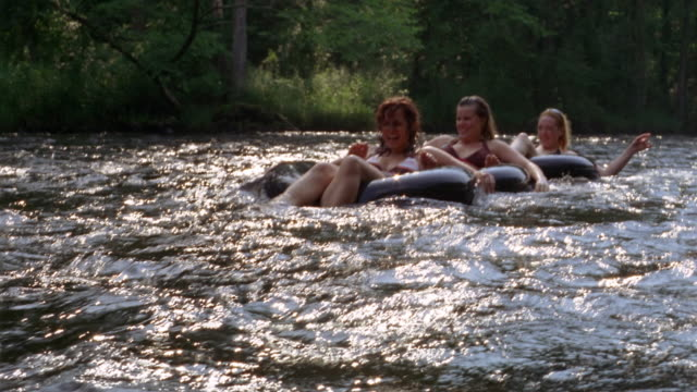 medium shot three women riding innertubes in a line on river - tubing stock videos and b-roll footage