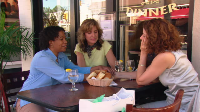 Medium shot three women sitting at outdoor cafe all holding hands on table/ Westfield, New Jersey
