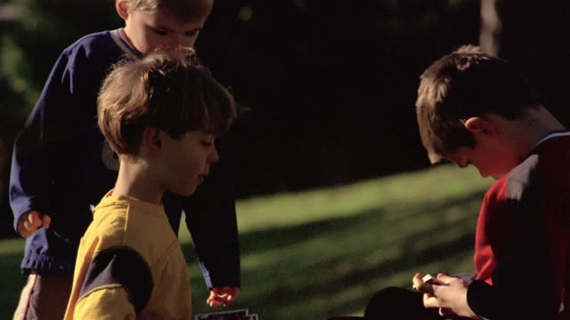 medium shot three young boys exchanging trading cards - exchanging stock videos & royalty-free footage