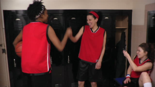 medium shot three young women basketball players giving each other street handshakes in locker room while one takes photo with camera phone / new york city, new york, usa - bench stock videos & royalty-free footage