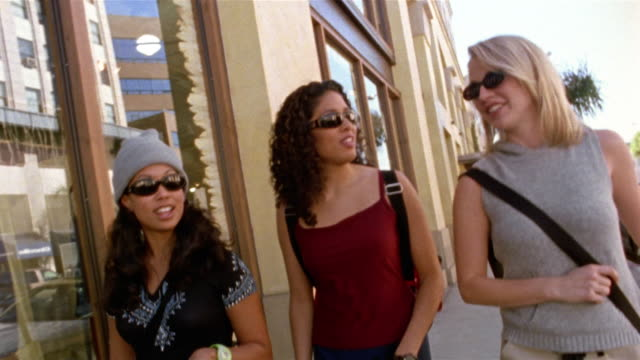 Medium shot three young women wearing sunglasses walking down street / pan rear view window shopping