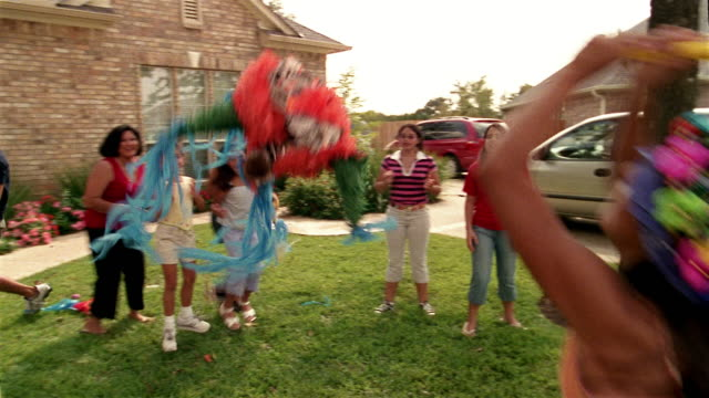 Medium shot tilt down blindfolded girl swinging at pinata / family gathered around cheering and diving for candy